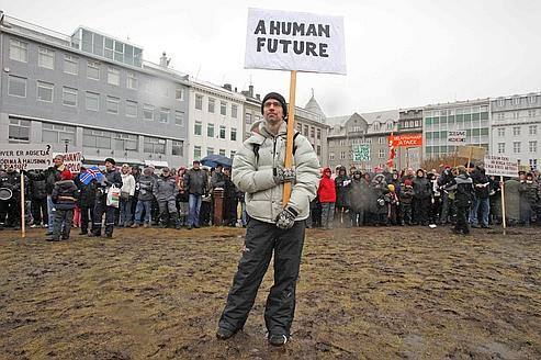 A demonstrator holds a sign during a protest against a government referendum in Reykjavi